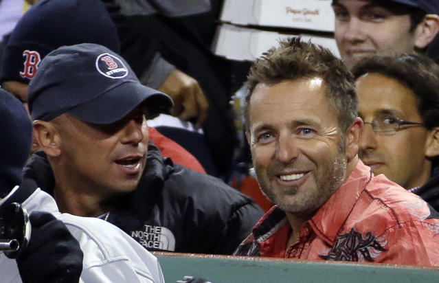 Former Boston Red Sox player Kevin Millar, right, watches with singer Kenny Chesney, left, during the seventh inning of Game 1 of baseball's World Series between the Boston Red Sox and the St. Louis Cardinals Wednesday, Oct. 23, 2013, in Boston. (AP Photo/Matt Slocum)