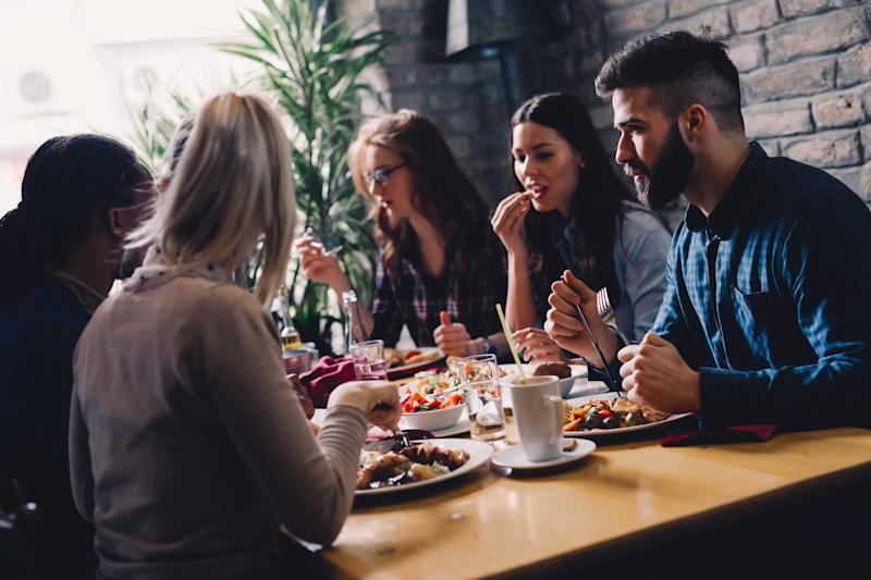 Group of people sitting at table eating.