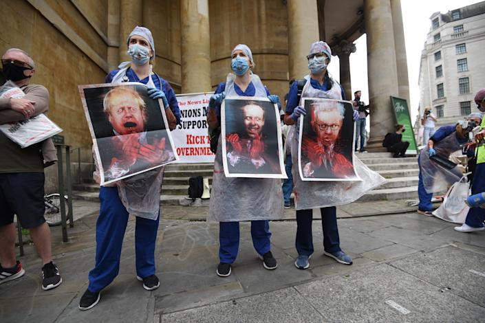 NHS workers hold pictures of the prime minister and other Cabinet members during the march (Picture: Getty)