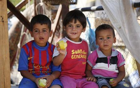 Syrian refugee children eat fruits under a tent at the Majdal Anjar refugee camp in Bekaa Valley, eastern Lebanon