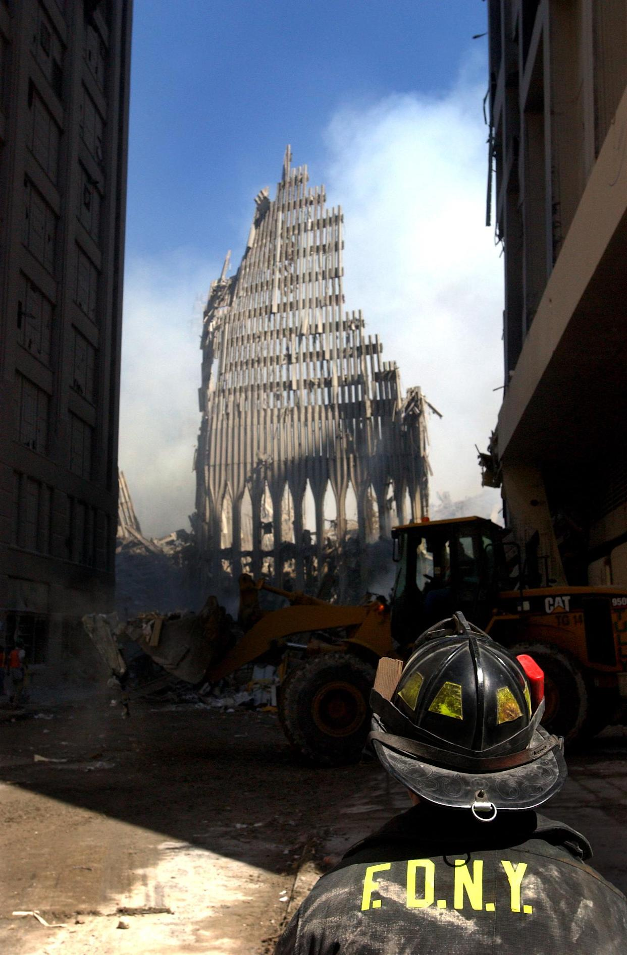 A New York City fire fighter looks up at what remains of the World Trade Center after its collapse following a Sept. 11 terrorist attack.  (U.S. Navy Photo by Photographer's Mate 2nd Class Jim Watson)