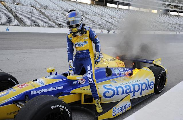Marco Andretti gets out of his car on the apron of Turn 4 as flames come from the rear of the car during the IndyCar auto race at Texas Motor Speedway in Fort Worth, Texas, Saturday, June 7, 2014. (AP Photo/Larry Papke)
