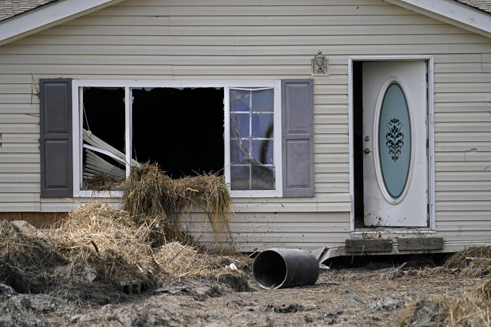 Marsh grass from flooding sits in a window of destroyed hom in Ironton, La., Monday, Sept. 27, 2021. A month after Hurricane Ida, small communities along Louisiana's southeastern coast are still without power or running water. Some residents have lost most of their possessions to the storm's floodwaters. (AP Photo/Gerald Herbert)