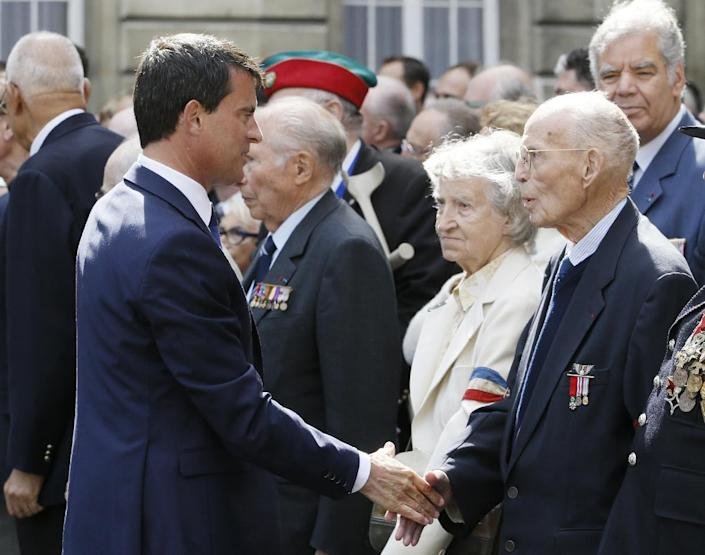 French Prime minister Manuel Valls greets veterans during a tribute ceremony commemorating the 70th anniversary events of Paris' liberation, on August 19, 2014 (AFP Photo/Patrick Kovarik)