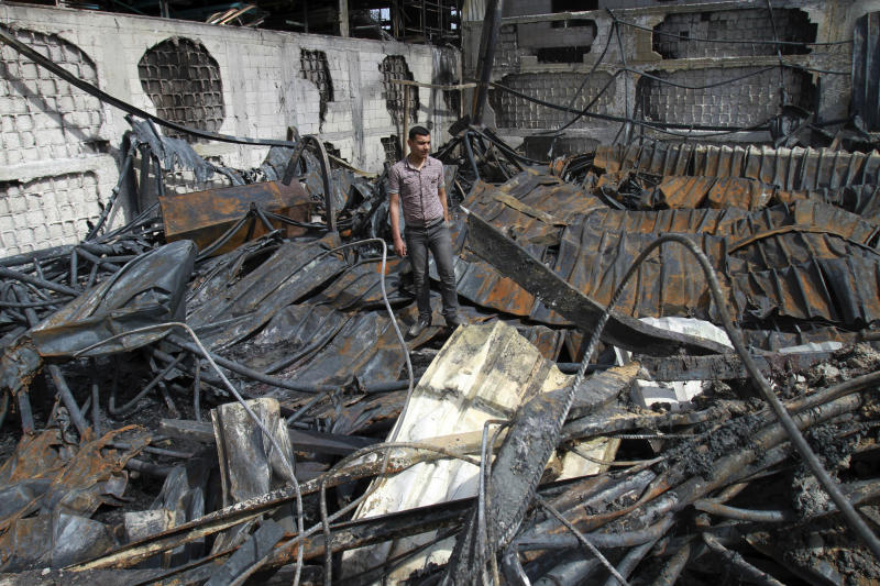 A Palestinian inspects a warehouse which caught fire after an Israeli air strike nearby in Gaza City, Wednesday, March 14, 2012. On Tuesday, Israel and Gaza militants agreed to a truce after four days of cross-border fighting, though there have been sporadic violations. (AP Photo/Adel Hana)
