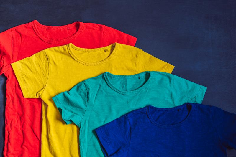 Colorful collection of t-shirts on wooden background.