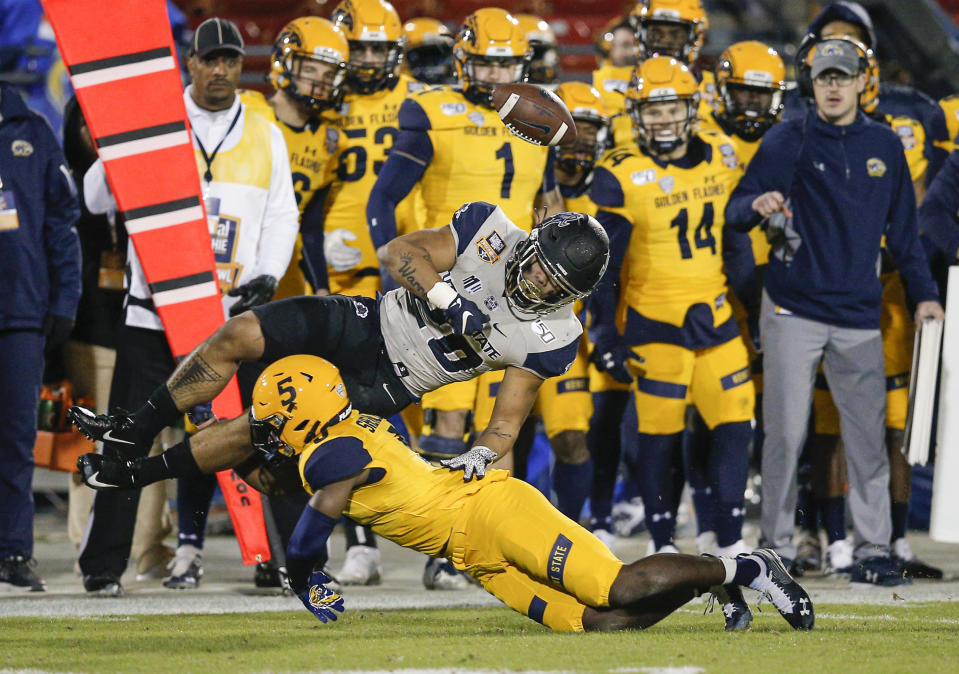 Utah State running back Jaylen Warren (20) fumbles the ball as Kent State cornerback Keith Sherald Jr. (5) makes the tackle during the first half of the Frisco Bowl NCAA college football game Friday, Dec. 20, 2019, in Frisco, Texas. Kent State linebacker Mandela Lawrence-Burke recovered the ball. (AP Photo/Brandon Wade)