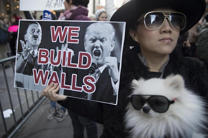 <p>Chong Cha demonstrates with her dog, Zuzu, during a rally outside Trump Tower in New York on Saturday, Nov. 12, 2016, to protest against President-elect Donald Trump. (AP Photo/Mary Altaffer) </p>