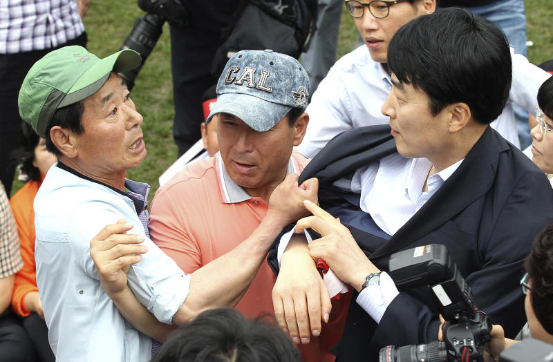 In this photo taken on Tuesday, July 3, 2012, a farmer grabs Lee Seok-ki, right, a lawmaker of the Unified Progressive Party during a rally to oppose the free trade agreement, or FTA, with the China in Seoul, South Korea. Lee's suggestion to replace the national anthem with a folk song popular in both Koreas has ignited a political and media firestorm from conservatives who are demanding that he be tossed out of parliament.  (AP Photo/Yonhap, Park Ji-ho) KOREA OUT
