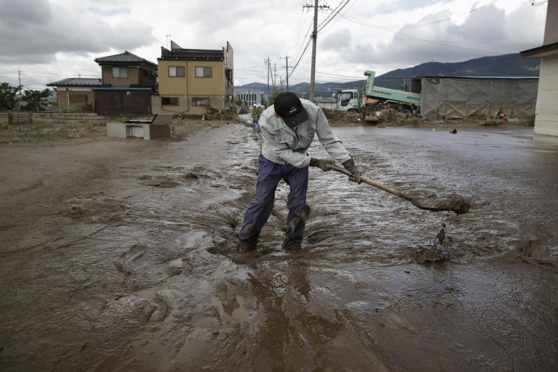 A man uses a shovel to scoop mud in a neighborhood devastated by Typhoon Hagibis, Oct. 15, 2019, in Nagano, Japan. (Photo: Jae C. Hong/AP)