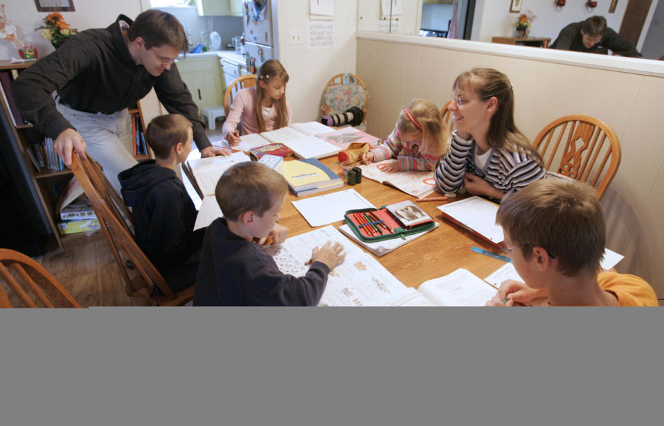FILE -- This March 13, 2009, file photo shows Uwe Romeike, top left, and his wife Hannelore, second from right, teaching their children at their home in Morristown, Tenn. A federal appeals court has denied asylum to the family that fled Germany so they could home-school their children, after ruling that U.S. immigration laws do not grant a safe haven to people everywhere who face restrictions that would be prohibited under the Constitution. (AP Photo/Wade Payne, File)