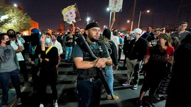 PHOTO: President Donald Trump supporters rally outside the Maricopa County Recorder's Office, Nov. 4, 2020, in Phoenix as two counter-protesters hold signs.  (Matt York/AP)
