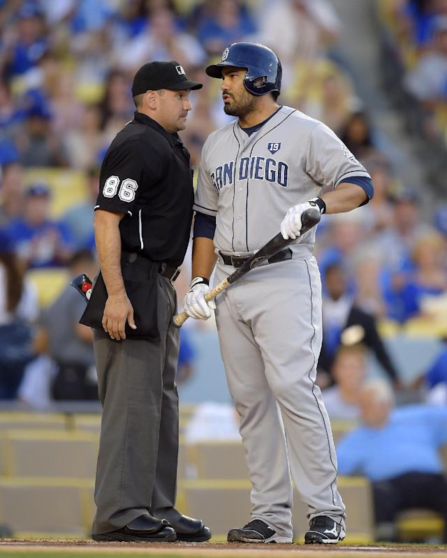San Diego Padres' Carlos Quentin, right, talks with home plate umpire David Rackley after striking out during the first inning of a baseball game against the Los Angeles Dodgers, Saturday, July 12, 2014, in Los Angeles. (AP Photo/Mark J. Terrill)