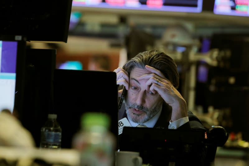 A trader talks on the phone while working on the floor of the New York Stock Exchange (NYSE) in New York