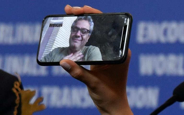 """A phone displays Iranian director Mohammad Rasoulof, who was awarded the 2020 """"Golden Bear for Best Film"""""""