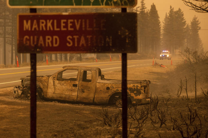 A scorched car rests on a roadside as the Tamarack Fire burns in the Markleeville community of Alpine County, Calif., on Saturday, July 17, 2021. (AP Photo/Noah Berger)