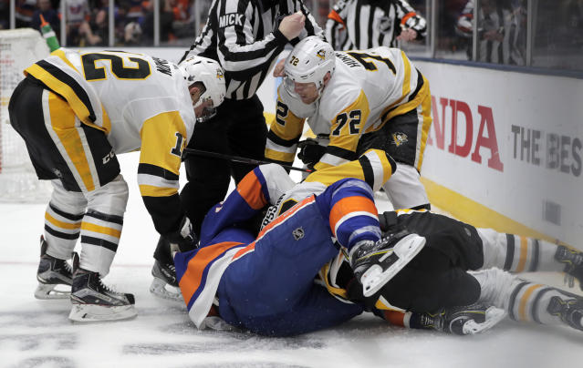 Pittsburgh Penguins center Dominik Simon (12), of the Czech Republic, and right wing Patric Hornqvist (72), of Sweden, pile on as defenseman Marcus Pettersson, bottom right, of Sweden, fights with New York Islanders center Mathew Barzal seconds after the Islanders scored a goal during the second period of Game 2 of an NHL hockey first-round playoff series Friday, April 12, 2019, in Uniondale, N.Y. (AP Photo/Julio Cortez)