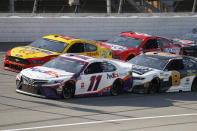 Denny Hamlin (11), Joey Logano (22), Kevin Harvick (4) and Tyler Reddick (8) compete during a NASCAR Cup Series auto race at Michigan International Speedway in Brooklyn, Mich., Saturday, Aug. 8, 2020. (AP Photo/Paul Sancya)