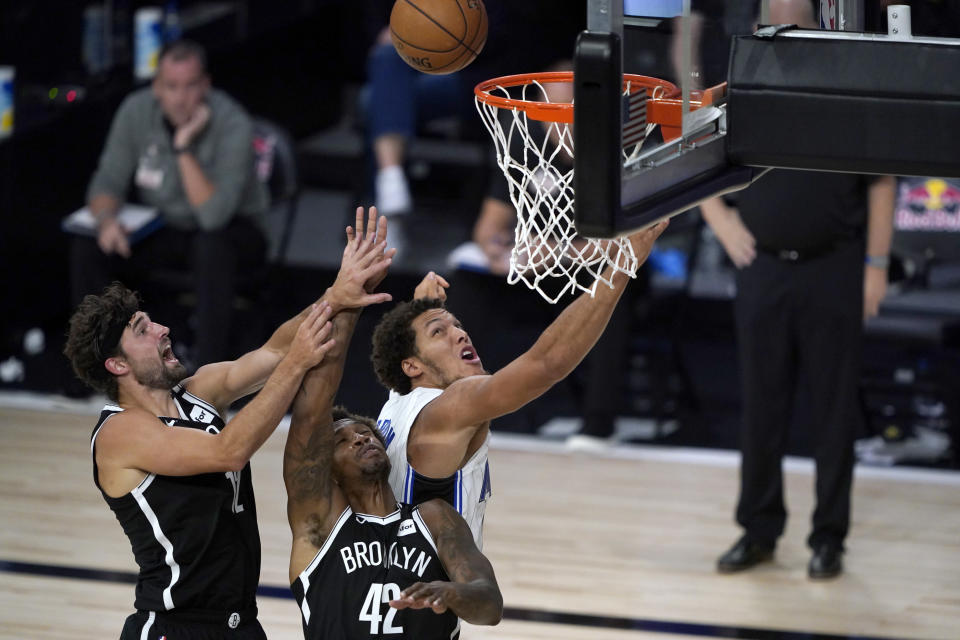 Orlando Magic's Aaron Gordon, right, watches a rebound with Brooklyn Nets' Lance Thomas (42) and Joe Harris, left, during the second half of an NBA basketball game Friday, July 31, 2020, in Lake Buena Vista, Fla. (AP Photo/Ashley Landis, Pool)