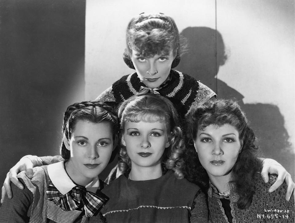American actress Katharine Hepburn (1907 - 2003) stands behind costars (left to right) Frances Dee (1909 - 2004), Joan Bennett (1910 - 1990), and Jean Parker as they pose for a publicity portrait to promote the film adaptation of Louisa May Alcott's book 'Little Women' directed by George Cukor, 1933. The four play the March girls. (Photo by RKO Pictures/Courtesy of Getty Images)