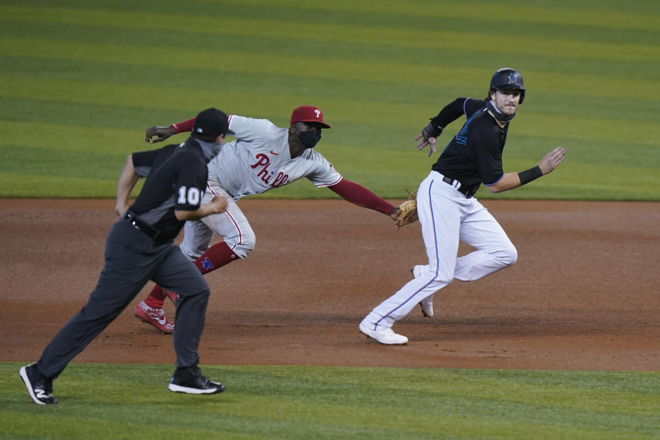 Philadelphia Phillies shortstop Didi Gregorius, center, tags out Miami Marlins' Brian Anderson as he attempted to advance to second during the first inning of the second game of a baseball doubleheader, Sunday, Sept. 13, 2020, in Miami. (AP Photo/Wilfredo Lee)
