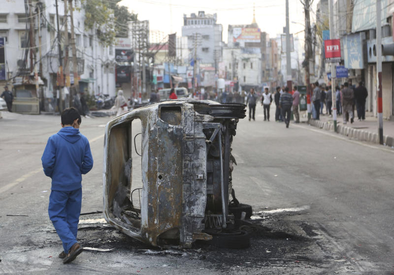 A boy walks past a vehicle burnt by a mob during a protest against Thursday's attack on a paramilitary convoy, in Jammu, India, Friday, Feb. 15, 2019. Thursday's attack on a paramilitary convoy in Kashmir has raised tensions in Hindu-majority India. Hundreds of residents carrying India's national flag in Hindu-dominated Jammu city in the Muslim-majority state burned vehicles and hurled rocks at homes in Muslim neighborhoods, officials said. (AP Photo/Channi Anand)