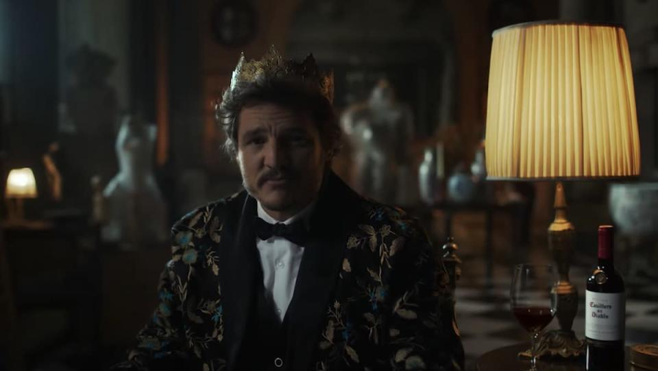 A man wearing a crown and robe sits next to a table with a bottle of wine, inside his giant mansion in this Pedro Pascal wine commercial