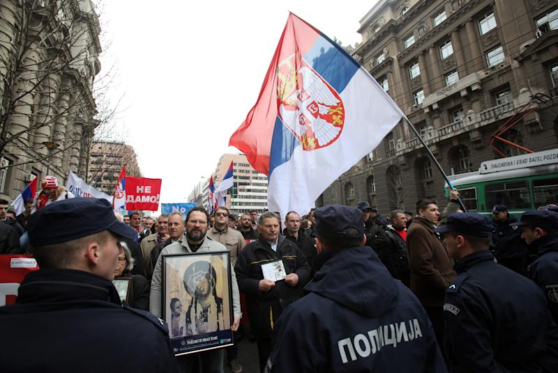 Protesters carry an icon and Serbian flags during the protest of Serbian nationalist organization Obraz (Honour) in front of the Government building in Belgrade, Serbia, Monday, April 8, 2013. Deputy Prime Minister Aleksandar Vucic says his government will reject an EU-brokered deal for Kosovo and will ask for more negotiations with ethnic Albanian leaders. The EU has given Serbia until Tuesday to say whether it would relinquish its control of northern Kosovo in exchange for the start of Serbia's EU membership negotiations. Serbia's government says it will give the answer later Monday. (AP Photo/Darko Vojinovic)