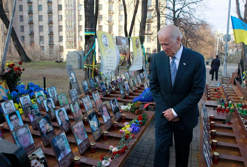 """US Vice President Joe Biden pays his respects to the """"Heavenly Hundred"""" -- Ukrainians killed during anti-government protests in 2013 and 2014 -- during a ceremony at their monument in Kiev on December 7, 2015 Joe Biden is in Ukraine for a three-day working visit. (AFP Photo/Sergei Chuzavkov)"""