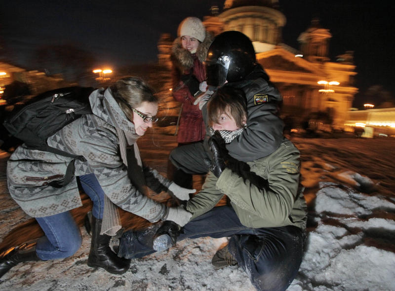 A Russian police officer detains an opposition activist as his friends try to free him during a protest against alleged vote rigging in St. Petersburg, Russia, Monday, March 5, 2012. More then 100 protesters were arrested in St. Petersburg, where some 2,000 gathered for an unauthorized rally to protest Russian Prime Minister Vladimir Putin's victory in Russian presidential election. (AP Photo/Dmitry Lovetsky)
