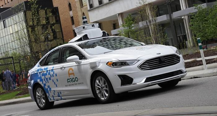 A white Ford Fusion sedan with visible self-driving sensor hardware and Argo AI logos on the doors, driving on a city street.