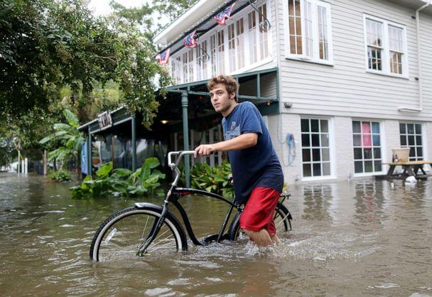 PHOTO: A man pushes his bike through a flooded street after Hurricane Barry in Mandeville, La., July 13, 2019. (Jonathan Bachman/Reuters)