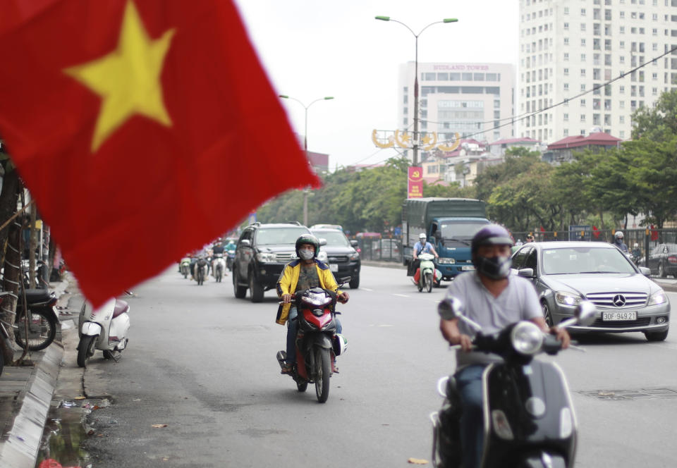 People wearing face masks to help curb the spread of the coronavirus ride mopeds in Hanoi, Vietnam on Thursday, Aug. 6, 2020. Vietnamese health official said on Thursday the COVID-19 outbreak would peak in the coming ten days as the country reported another death and a score of new infections. (AP Photo/Hau Dinh)