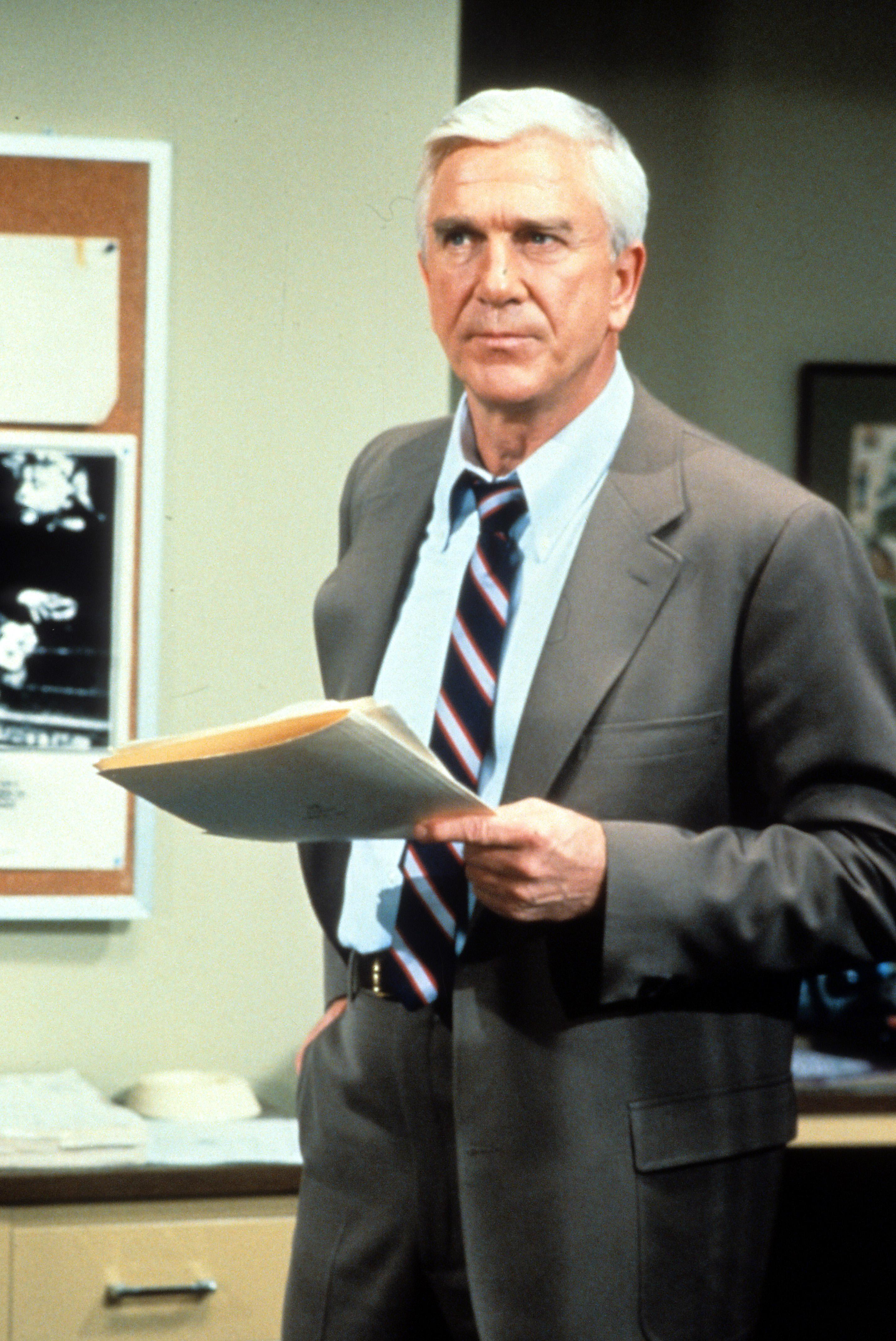 Leslie Nielsen holding folders in a scene from the television series 'Police Squad!', 1982. (Photo by Paramount/Getty Images)