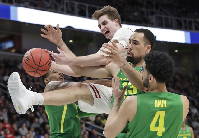Wisconsin forward Nate Reuvers, top, reaches for a rebound over Oregon forward Paul White, second from right, and guard Ehab Amin (4) during the second half a first-round game in the NCAA mens college basketball tournament, Friday, March 22, 2019, in San Jose, Calif. (AP Photo/Chris Carlson)