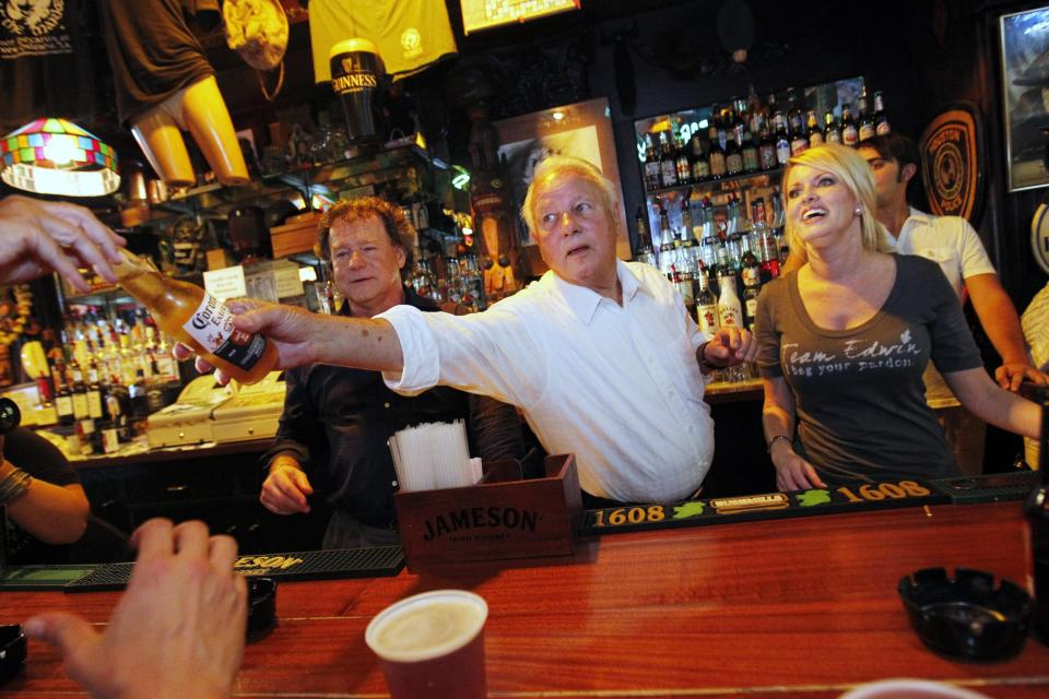In this Aug. 23, 2011, photo, former Louisiana Governor Edwin Edwards, 84, and his wife Trina Scott Edwards, 32, right, serve as honorary bartenders at Molly's On The Market Bar during a Press Club of New Orleans function in New Orleans. Edwin Washington Edwards, the high-living four-term governor whose three-decade dominance of Louisiana politics was all but overshadowed by scandal and an eight-year federal prison stretch, died Monday, July 12, 2021 . He was 93. Edwards died of respiratory problems with family and friends by his bedside, family spokesman Leo Honeycutt said. He had suffered bouts of ill health in recent years and entered hospice care this month at his home in Gonzales, near the Louisiana capital. (AP Photo/Gerald Herbert)