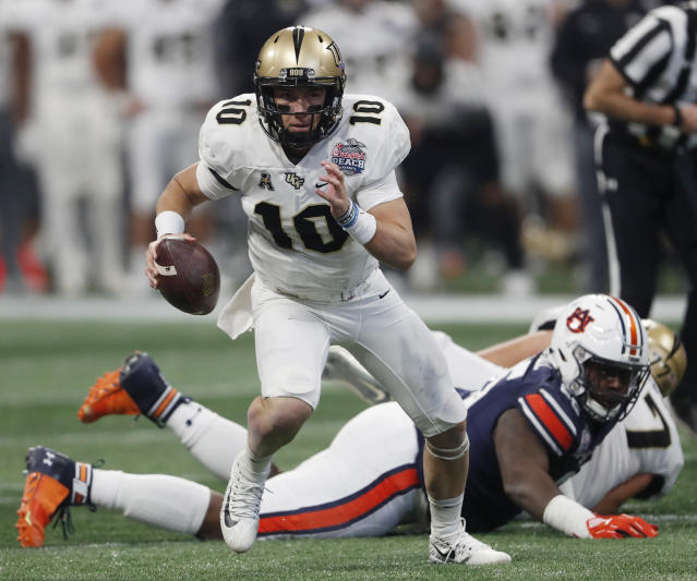 "Central Florida quarterback <a class=""link rapid-noclick-resp"" href=""/ncaaf/players/270182/"" data-ylk=""slk:McKenzie Milton"">McKenzie Milton</a> (10) runs out of the pocket against Auburn during the first half of the Peach Bowl NCAA college football game, Monday, Jan. 1, 2018, in Atlanta. (AP Photo/John Bazemore)"