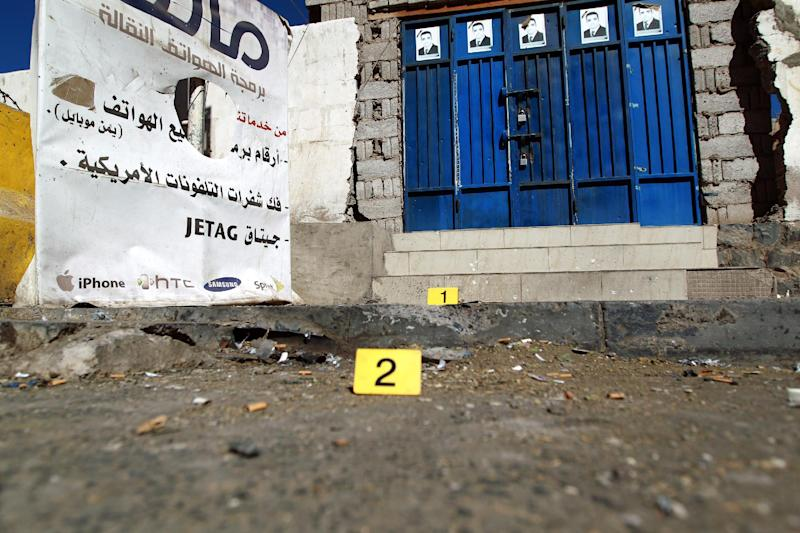 Yellow numbered markers are seen on the ground at the site of a bomb blast at the entrance of the presidential palace in Sanaa on February 7, 2015 (AFP Photo/Mohammed Huwais)