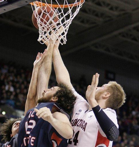 Lewis-Clark State's Nick Fromm, front left, and Gonzaga's Przemek Karnowski, right, battle for a rebound during the second half of an NCAA college basketball game in Spokane, Wash., Thursday, Nov. 29, 2012. Gonzaga won 104-57. (AP Photo/Young Kwak)