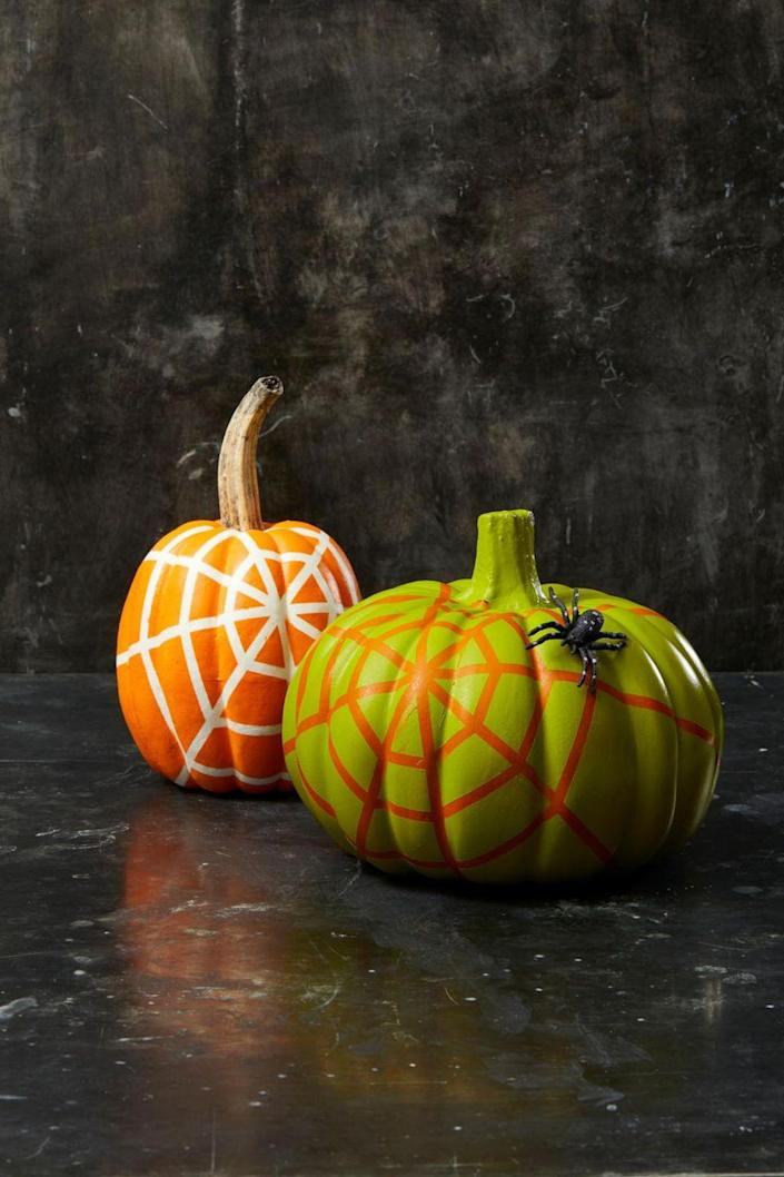 """<p>Create a spiderweb pattern by using long strips of tape, then spray paint over them. Once it's dry, peel off the tape to reveal a spooky, Halloween-ready design!</p><p><strong><em>Get the tutorial from <a href=""""https://www.goodhousekeeping.com/holidays/halloween-ideas/g2592/pumpkin-painting-ideas"""" rel=""""nofollow noopener"""" target=""""_blank"""" data-ylk=""""slk:Good Housekeeping"""" class=""""link rapid-noclick-resp"""">Good Housekeeping</a>.</em></strong></p>"""