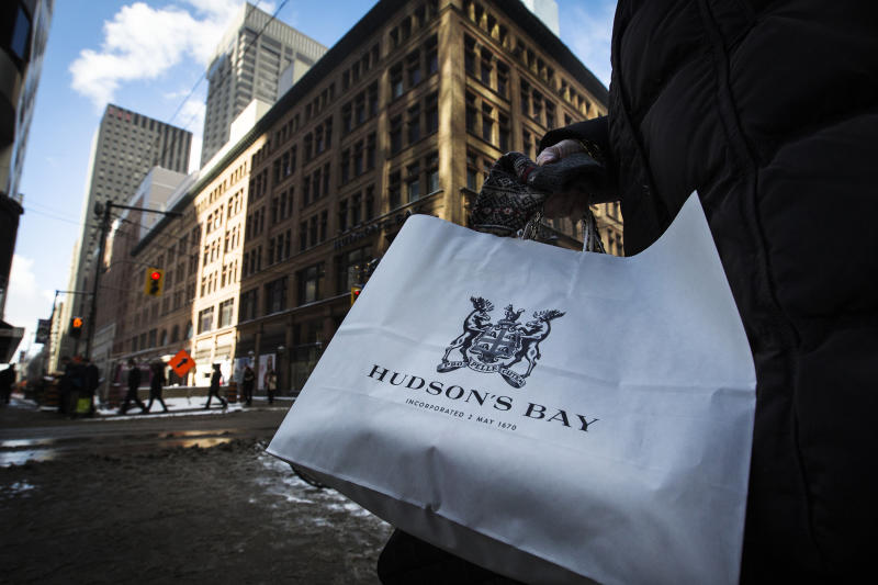 A woman holds a Hudson's Bay shopping bag in front of the Hudson's Bay Company (HBC) flagship department store in Toronto January 27, 2014. Hudson's Bay Co said on Monday that it would sell its flagship downtown Toronto store and neighboring executive offices for C$650 million ($587.09 million) to Cadillac Fairview Corp and open a full-line Saks store in the leased-back space. The Canadian retailer, which completed its $2.4 billion purchase of U.S. luxury chain Saks Inc late last year, said it expects to open an approximately 150,000 square-foot, multi-level Saks in the fall of 2015, co-located with the current Hudson's Bay store. REUTERS/Mark Blinch (CANADA - Tags: BUSINESS)