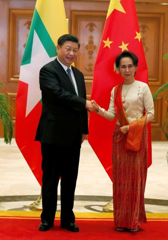 Myanmar State Counselor Aung San Suu Kyi shakes hands with Chinese President Xi Jinping at the Presidential Palace in Naypyitaw