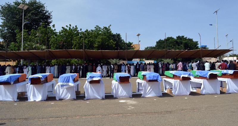 The coffins of nine United Nations soldiers are draped with Niger and UN flags during a service in Niamey on October 8, 2014 (AFP Photo/Boureima Hama)