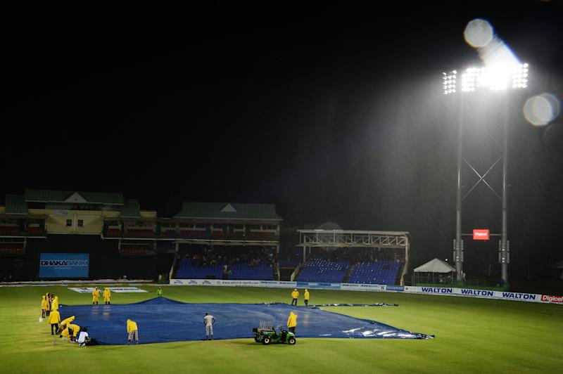 Workers cover the field for a rain delay during a T20 International between the West Indies and Bangladesh, at the Warner Park cricket ground in Basseterre, Saint Kitts and Nevis, on August 27, 2014