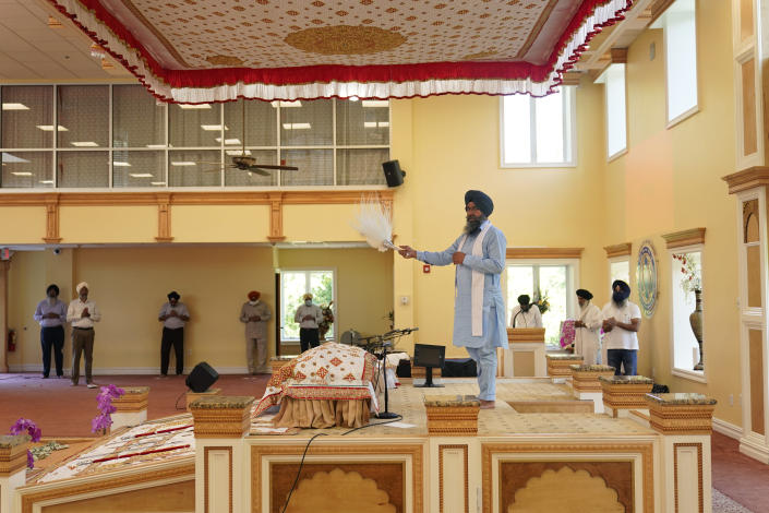 """Raghuvinder Singh, center, participates in a Sikh worship service at a gurdwara in Glen Rock, N.J., Sunday, Aug. 15, 2021. Baba Punjab Singh, a Sikh priest visiting from India, was shot in the head by a white supremacist Army veteran in Wisconsin in 2012, and left partially paralyzed. He died from his wounds in 2020. Over seven years, the priest's son, Raghuvinder Singh, split his time between caring for his father in Oak Creek and working in Glen Rock, New Jersey, as assistant priest at a gurdwara there. Raghuvinder said the greatest lesson his father taught him was how to embody """"chardi kala,"""" which calls for steadfast optimism in the face of oppression. (AP Photo/Seth Wenig)"""