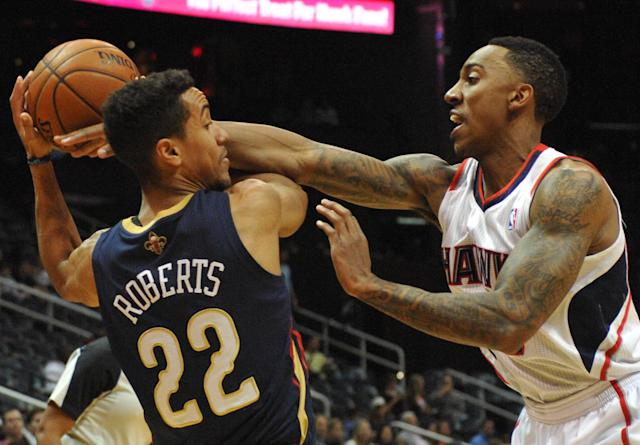 Atlanta Hawks' Jeff Teague, right, tries to steal the ball from New Orleans Pelicans' Brian Roberts (22) in the first half of their NBA basketball game Friday, March 21, 2014, in Atlanta. (AP Photo/David Tulis)