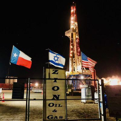 Flags of Texas, Israel, and the United States fly at night on January 26, 2021, in front of Zion's drilling rig in Israel.