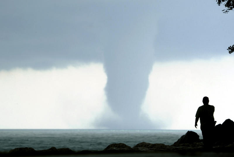 A person takes photos of a large water spout on Lake Michigan south east of Kenosha, Wis. on Thursday, Sept. 12, 2013. At times two separate spouts were visible as clouds rotated. The National Weather Service in Sullivan said the water spouts occurred about four miles southeast from Kenosha. A water spout is basically a tornado over water, meteorologist Ed Townsend said. (AP Photo/The Kenosha News, Kevin Poirier)
