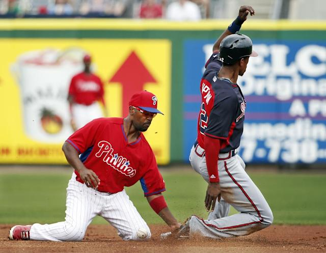 Atlanta Braves B.J. Upton, right, slides safely into second on a steal during the first inning as Philadelphia Phillies shortstop Jimmy Rollins bobbles the ball in a spring exhibition baseball game in Clearwater, Fla., Monday, March 10, 2014. The Braves won 8-1. (AP Photo/Kathy Willens)