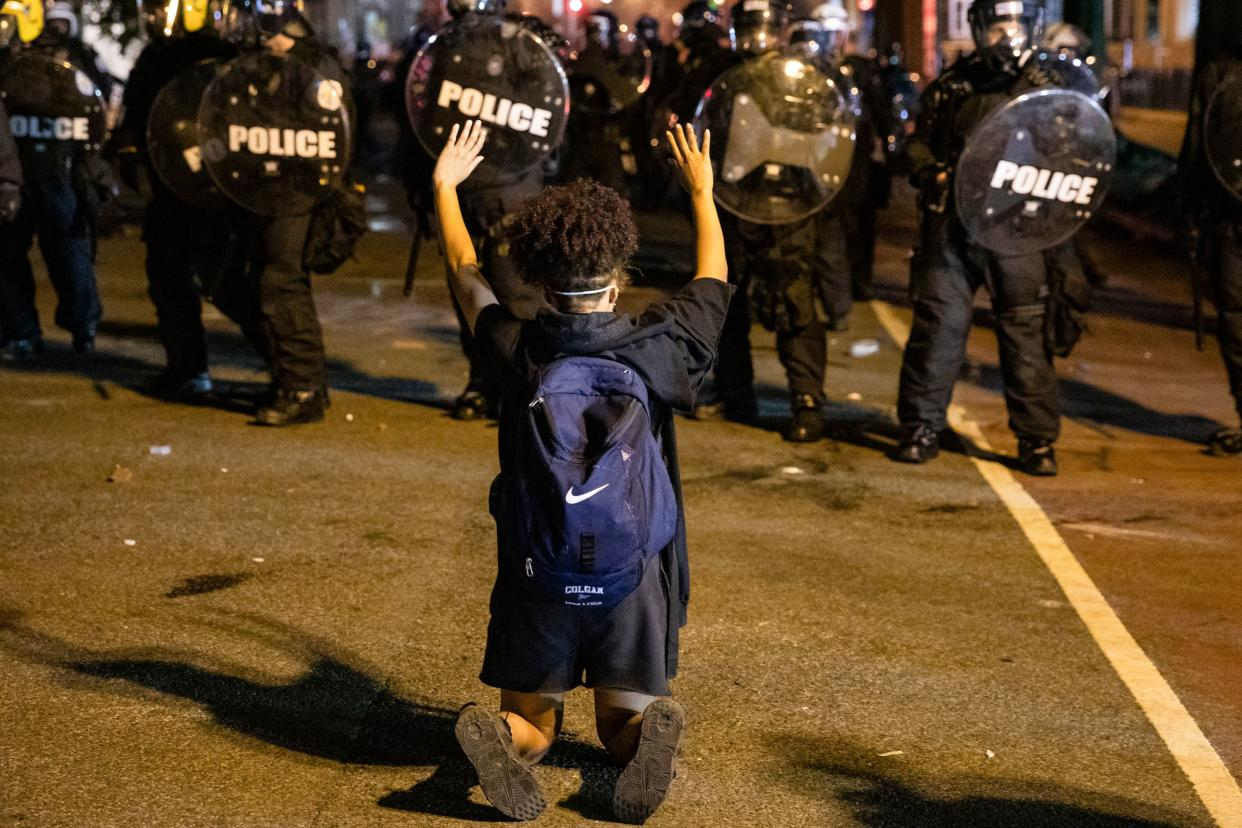 A demonstrator kneels and raises her hands facing a  police line